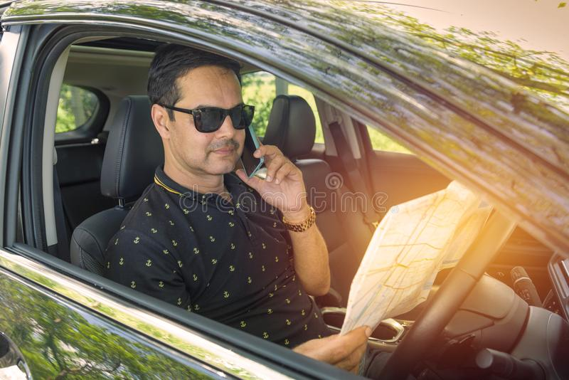 Muslim business man in casual dress sit in car hand use smart ph. One and look in map stock photography