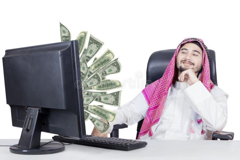 Muslim businessman looking money on monitor royalty free stock photo