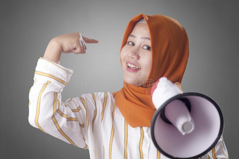 Muslim Businesswoman Calling or Offering Something with Megaphone, Advertising Marketing Concept. Portrait of Asian muslim woman calling or offering something royalty free stock images