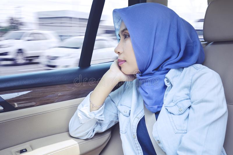 Muslim businesswoman looks pensive in the car stock photography