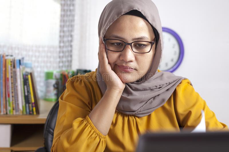 Muslim Businesswoman Seriously Working. Portrait of young Asian muslim businesswoman seriously analyzing reading business chart report in office indonesian royalty free stock images
