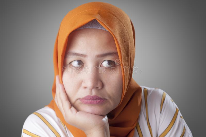 Muslim Businesswoman Thinking Something, Hand Under Chin. Asian muslim businesswomen wearing hijab with curiousity thinking expression. Looking for solution of a stock image