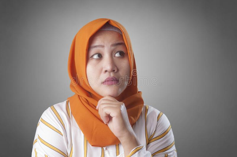 Muslim Businesswoman Thinking Something, Having Bright Idea. Asian muslim businesswomen wearing hijab with curiousity thinking expression. Having good idea royalty free stock images