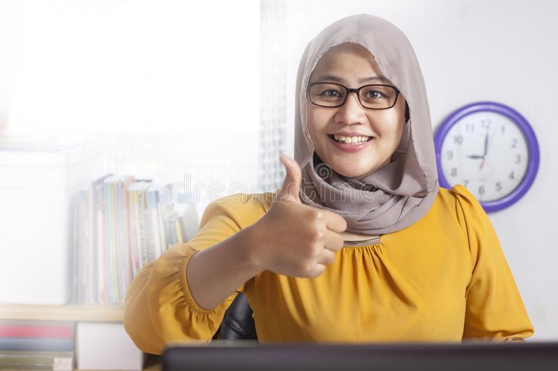 Muslim Businesswoman Working on Laptop at the Office, Smiling and Thumb Up stock photography