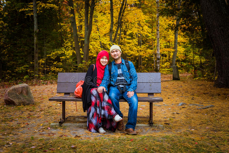 Muslim couple during autumn season. Muslim couple with colourful trees as background during autumn season stock photography