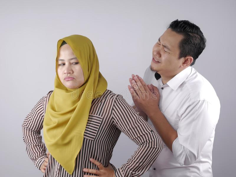 Husband Trying to Persuade and Apologize to His Wife. Muslim couple having conflict, husband trying to resolve, persuade and apologize to his wife after fight royalty free stock photos