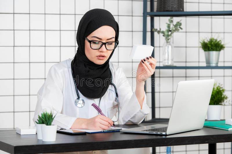 A Muslim Doctor with glasses and stethoscope working with documents on a white background.  royalty free stock image