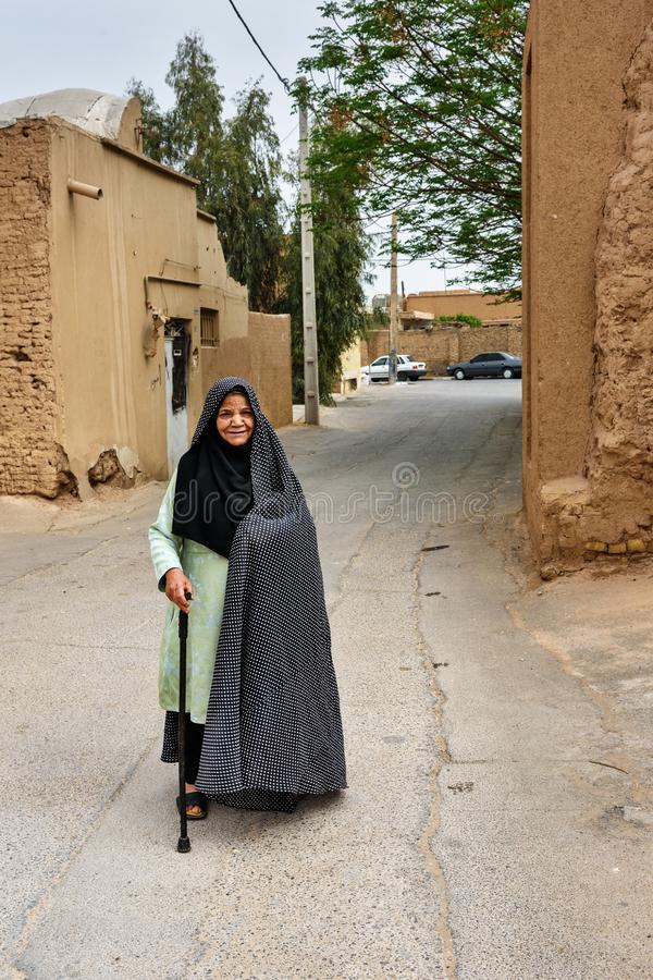 Muslim elderly woman, dressed in black chador on the street of old town in Yazd. Iran stock photography