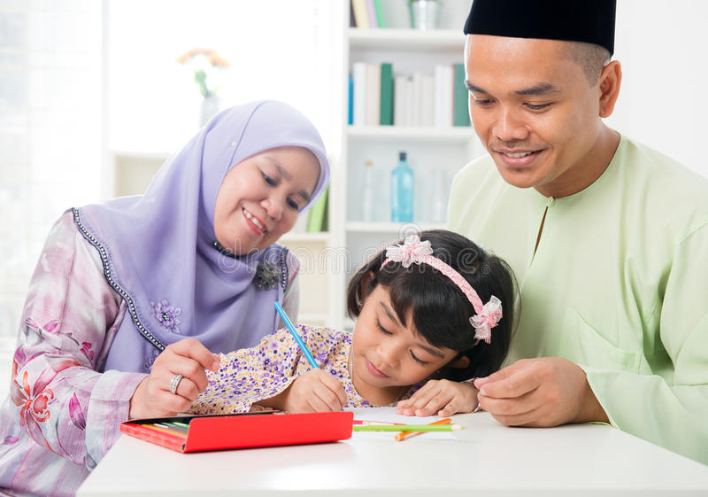 Muslim family drawing and painting. Picture at home. Southeast Asian family lifestyle. Happy smiling parents and child royalty free stock photos
