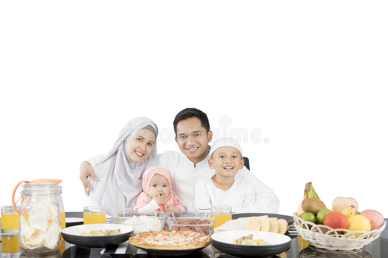 Muslim family having meal at dining table. While smiling at the camera, isolated on white background stock photography