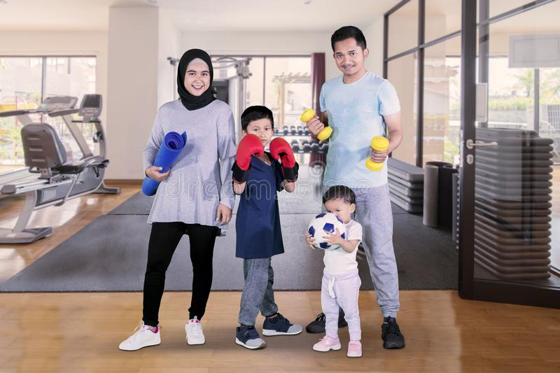 Muslim family holding different sports equipment stock photography