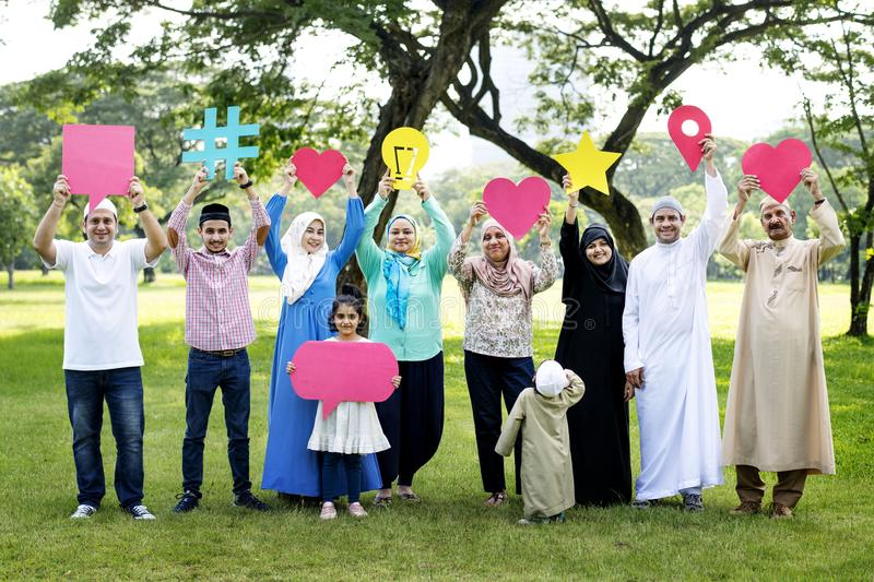 Muslim family holding up various social media icons stock photography