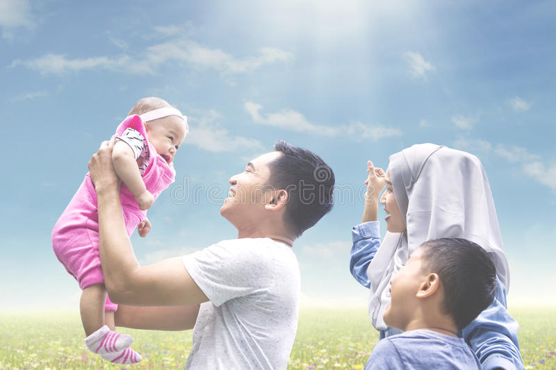 Muslim family playing with baby on meadow stock photos