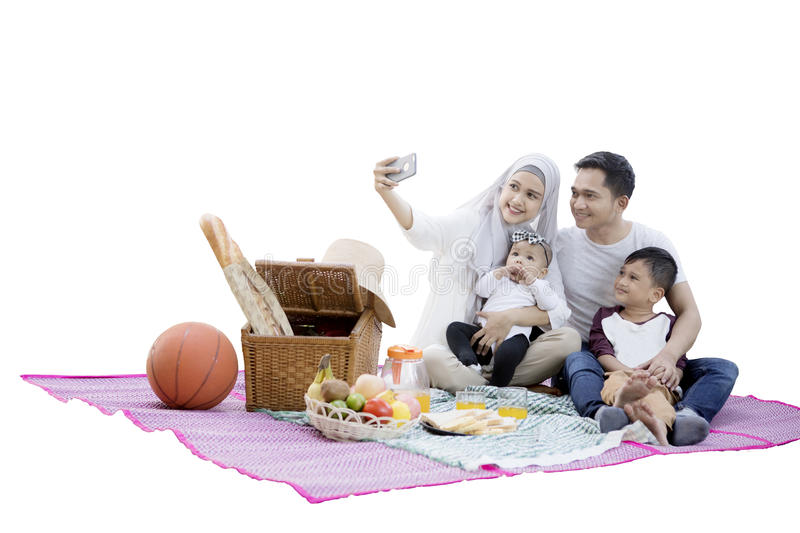 Muslim family takes self pictures. Portrait of Muslim family using a smartphone to take self pictures while enjoying a picnic in the studio stock photography