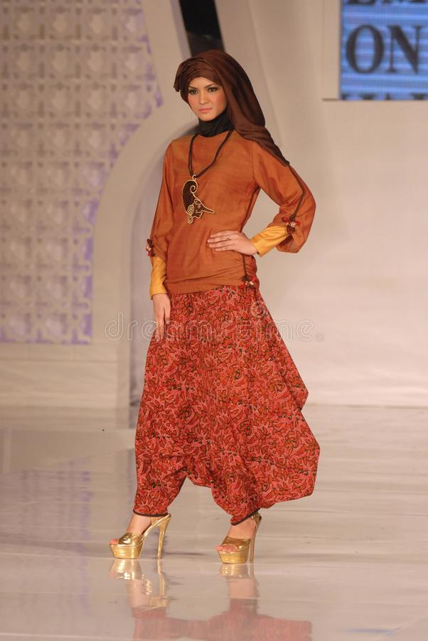 Muslim Fashion Festival 2014. A model showcases designs by Alphiana Candrajani on the runway at the 5th Muslims Fashion Festival 2014 show on October 3, 2014 in stock photos