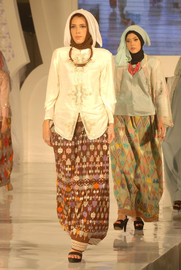 Muslim Fashion Festival 2014. Models showcase designs by Dwi Adi Kusuma on the runway at the 5th Muslims Fashion Festival 2014 show on October 3, 2014 in royalty free stock images