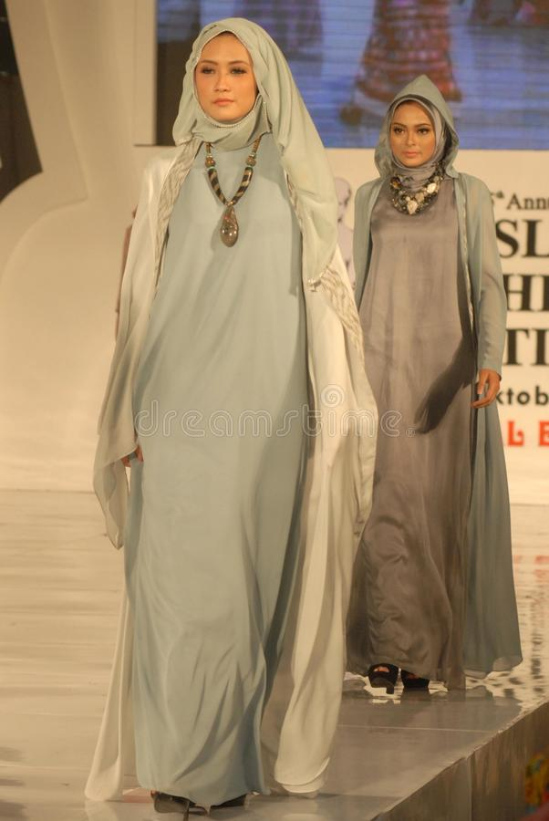 Muslim Fashion Festival 2014. Models showcase designs by Dwi Adi Kusuma on the runway at the 5th Muslims Fashion Festival 2014 show on October 3, 2014 in royalty free stock photos