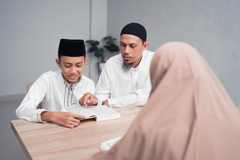 Muslim father teaching his son how to read quran. Portrait of a muslim father teaching his son how to read quran stock photo