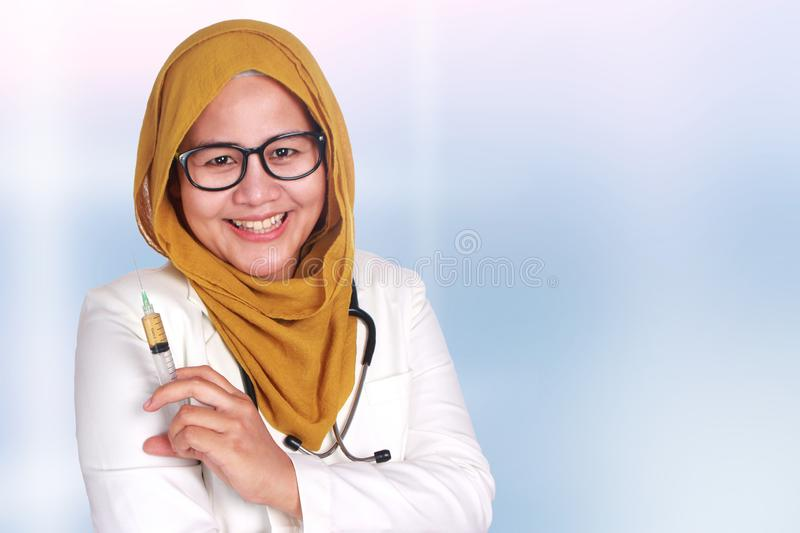 Muslim Female Doctor Holding Injection Syringe. Portrait of female Asian muslim doctor smiling when holding injection syringe, clinic, care, girl, adult, woman stock photography