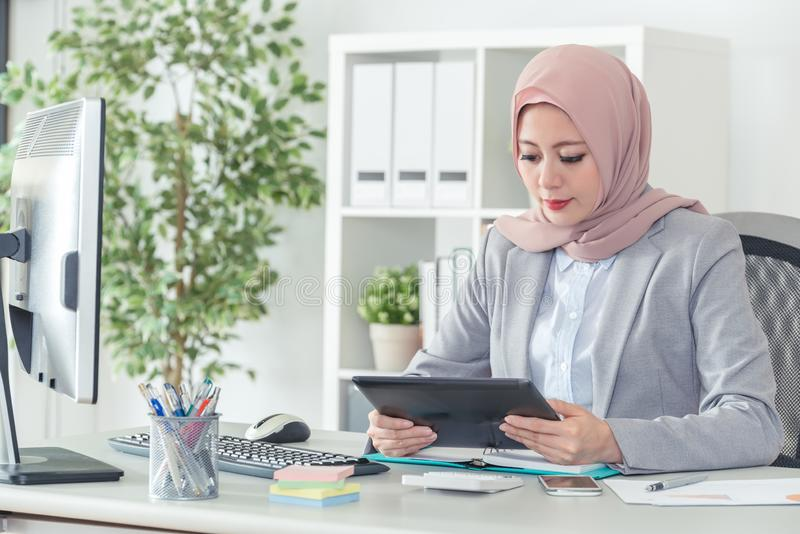 Businesswoman busy working on digital pad. Muslim female employee looking at the tablet and thinking for the next plan.Serious businesswoman busy working on stock image