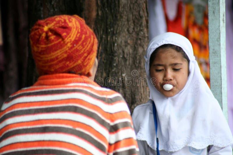 Muslim girl chewing gum stock image