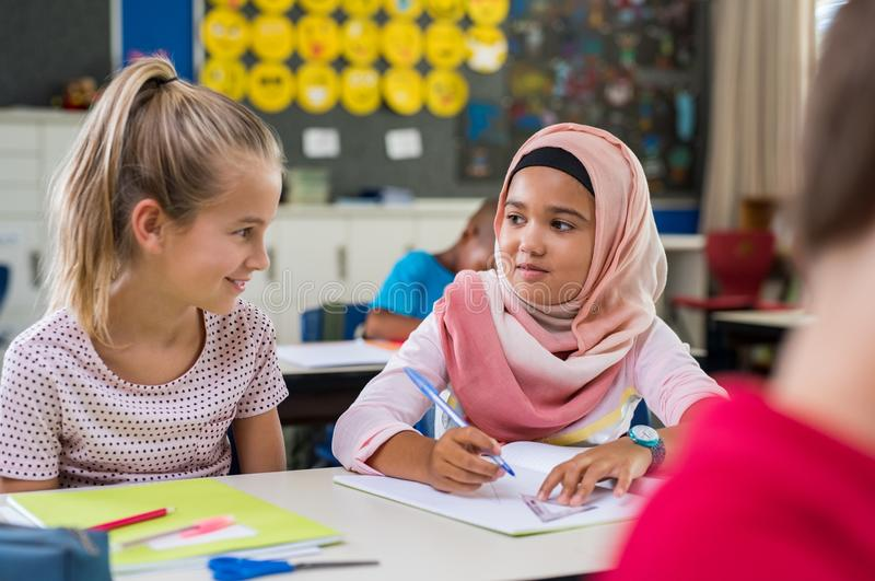 Muslim girl with her classmate. Young arab girl with hijab doing exercise with her bestfriend at international school. Asian muslim school girl sitting near her stock photos