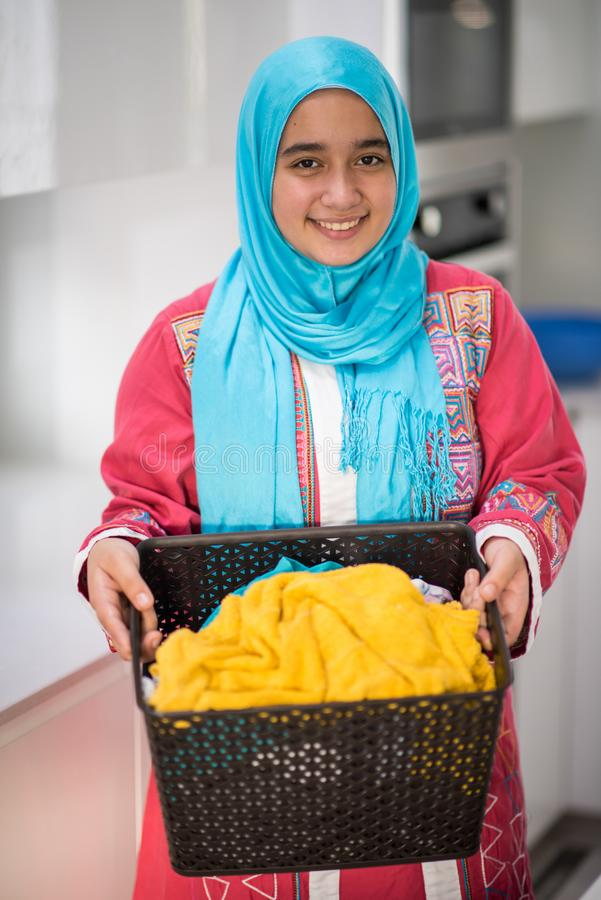 Muslim girl with laundry. Cleaning home stock image