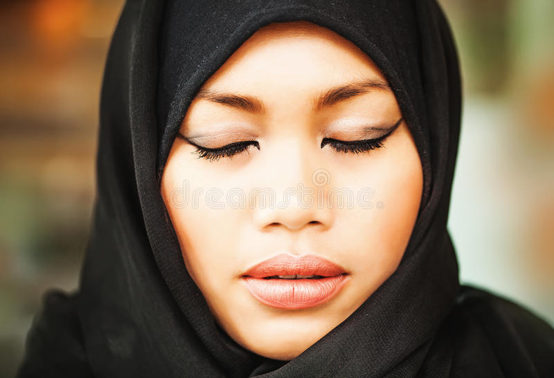 Muslim indonesian woman with closed eyes stock photography