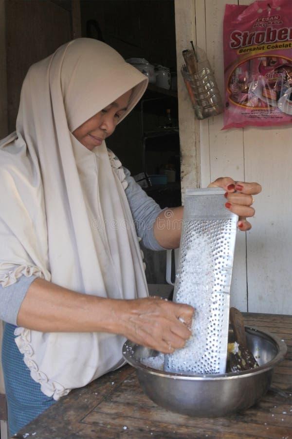 Muslim Indonesian woman grating coconut fruit in Gili Air Island Indonesia. Muslim Indonesian woman grating coconut fruit. Indonesia has the largest Muslim royalty free stock photos