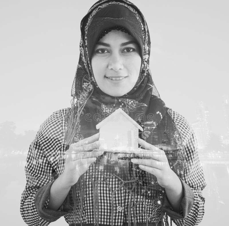 Muslim agent woman buying renting apartment or house real estate double exposure with city background. Muslim islam agent woman buying renting apartment or house stock images