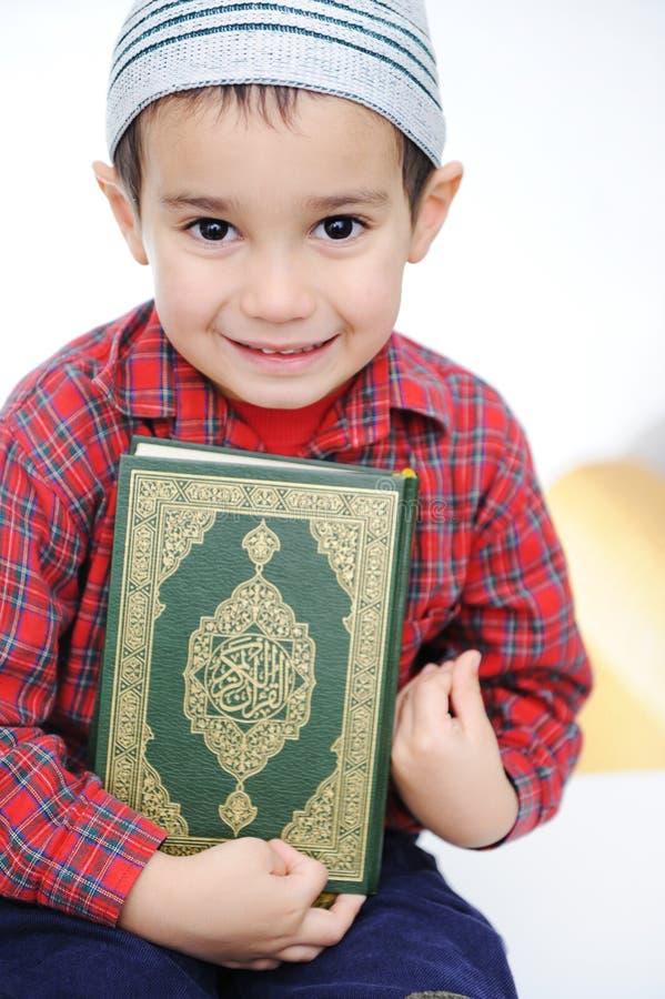 Muslim kid with holy Koran stock photos