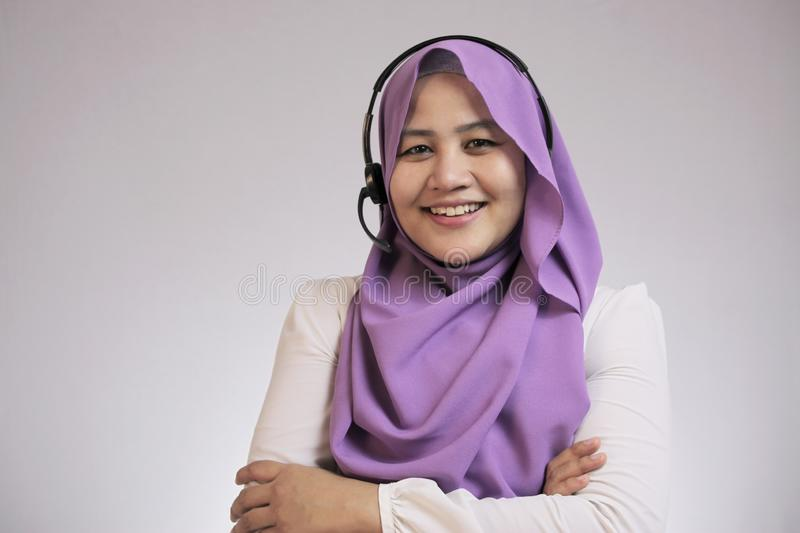 Muslim Lady Call Center Operator Smiling at Camera. Portrait of beautiful young muslim lady wearing hijab, call center operator consultant smiling with royalty free stock photography