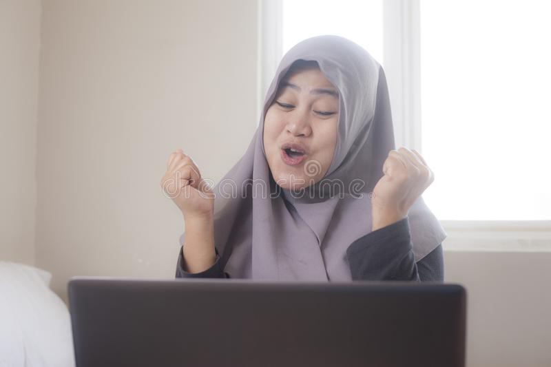 Muslim Lady Shows Winning Gesture, Receiving Good News on Her Email. Portrait of Asian muslim lady shows happy surprised expression celebrating winning victory stock images