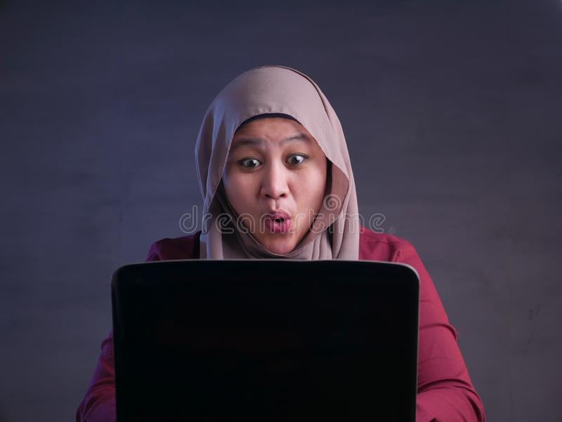 Muslim Lady Shows Winning Gesture, Receiving Good News on Her Email. Portrait of Asian muslim lady shows happy surprised expression celebrating winning victory royalty free stock photography