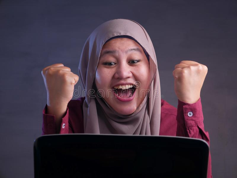 Muslim Lady Shows Winning Gesture, Receiving Good News on Her Email. Portrait of Asian muslim lady shows happy surprised expression celebrating winning victory stock photos