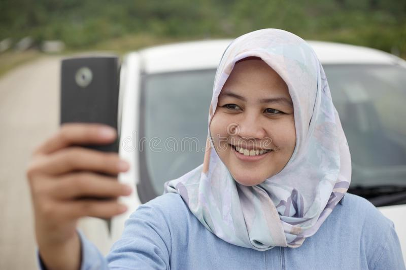 Muslim Lady Taking Selfie Photo With her Smart Phone in The Car. Portrait of Asian muslim lady smiling while taking selfie photo picture with smart phone in her stock photography