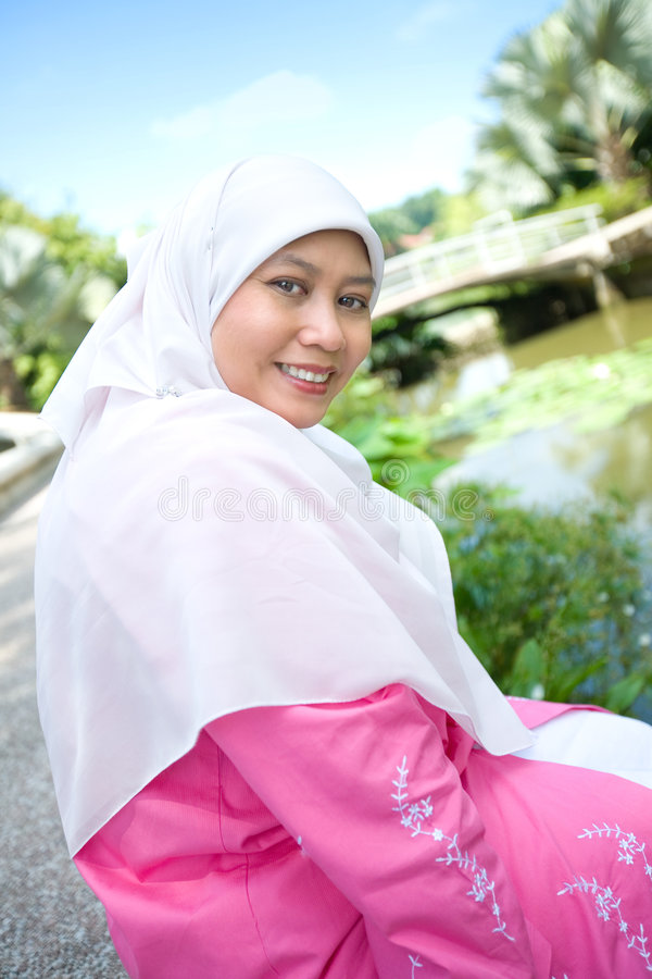 Muslim Malay woman smiling in an outdoor park stock image
