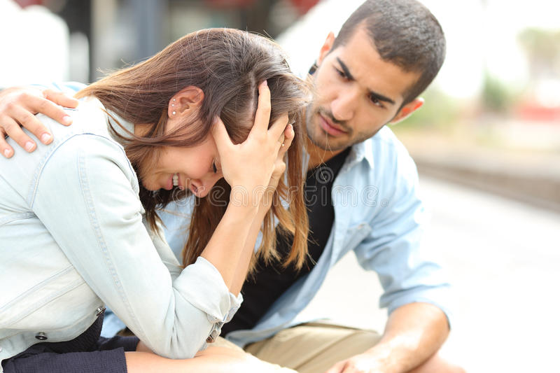 Muslim man comforting a sad girl mourning stock images