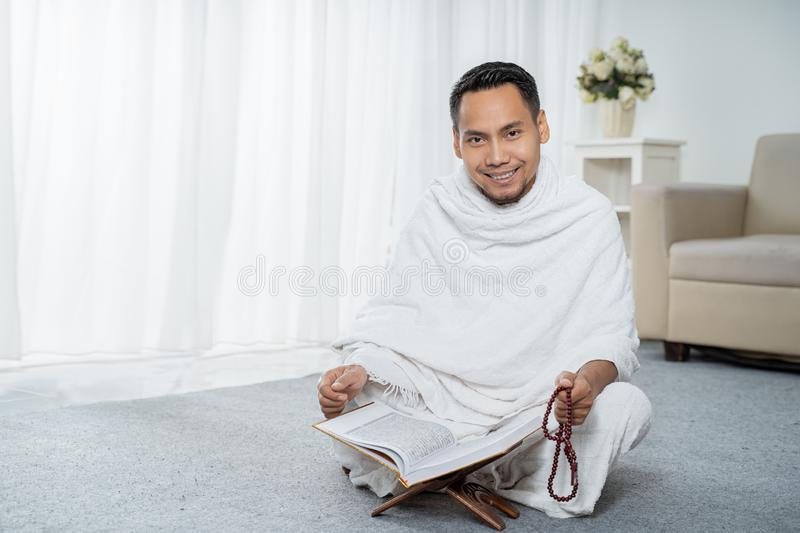 Muslim man praying with tasbih. In white traditional clothes stock image