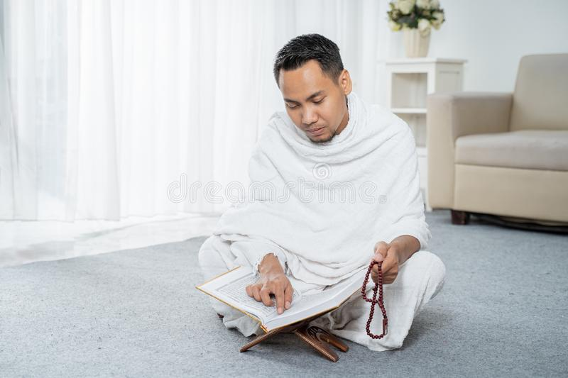 Muslim man praying in white traditional clothes. Muslim man praying while sitting in white traditional clothes stock image
