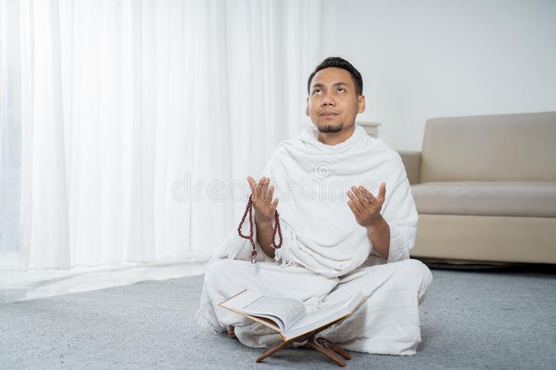 Muslim man praying in white traditional clothes. Muslim man praying while sitting in white traditional clothes royalty free stock photos