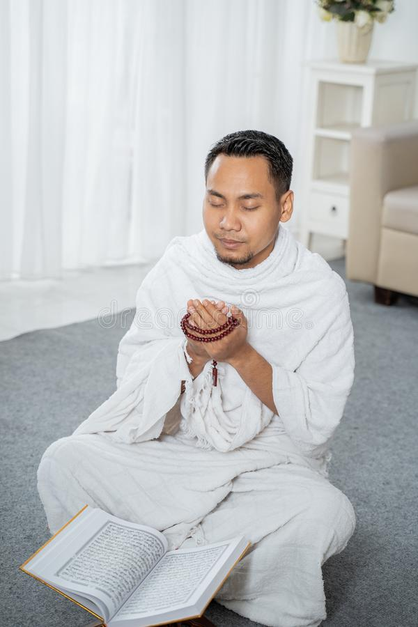 Muslim man praying in white traditional clothes. Muslim man praying while sitting in white traditional clothes royalty free stock image