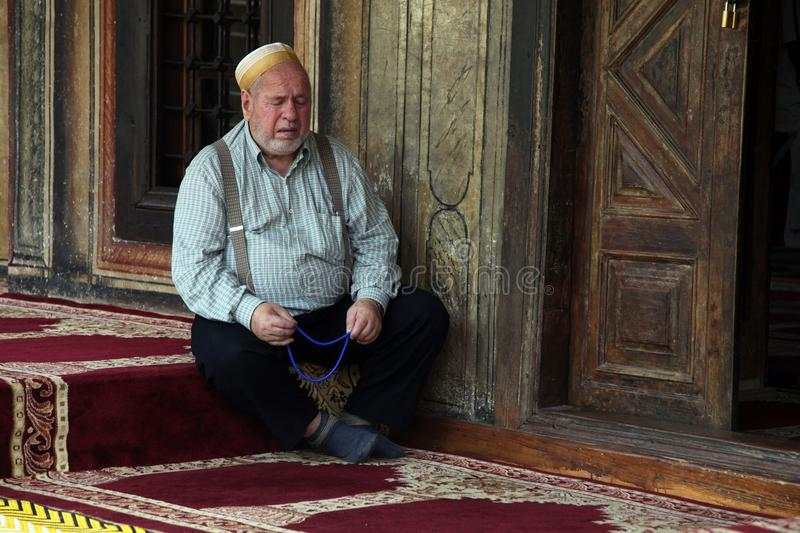 Muslim man seating in front mosque,Tetovo, Macedonia. Muslim man seating in front Aladza painted mosque,Tetovo, Macedonia stock images