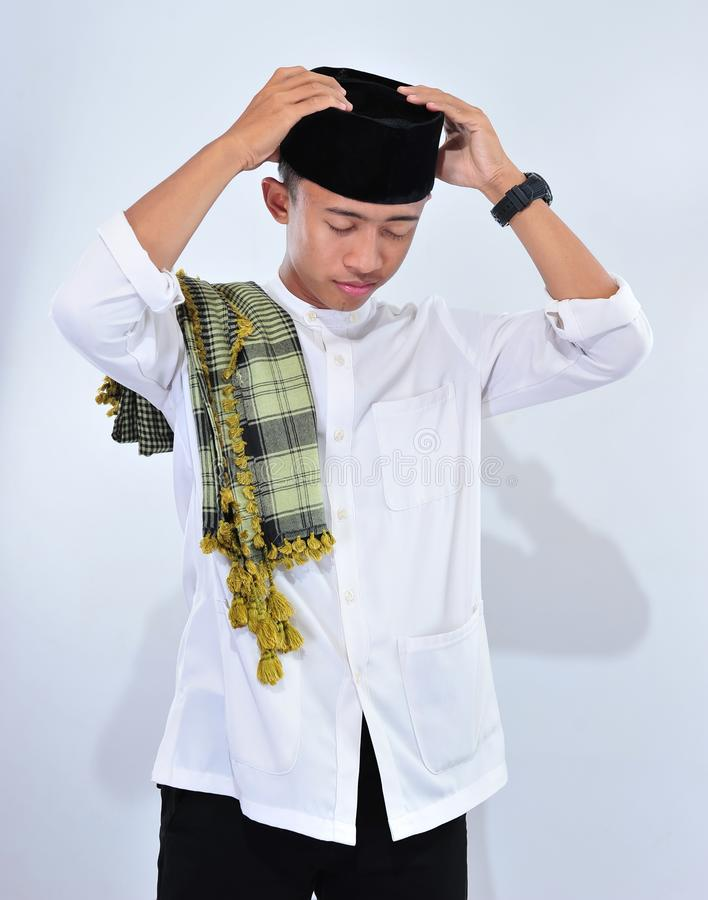 Muslim man wear a skull cup and white traditional clothes in ied mubarak celebration stock photography