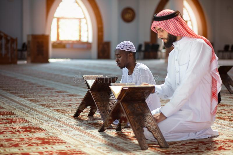 Muslim men praying with holy books in mosque royalty free stock photography