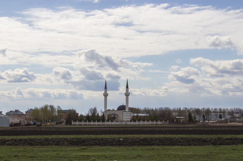 Muslim mosque with two minarets in Tatar village Russia. White mosque on cloudy sky, dome and two minarets Muslim shrine stock photos