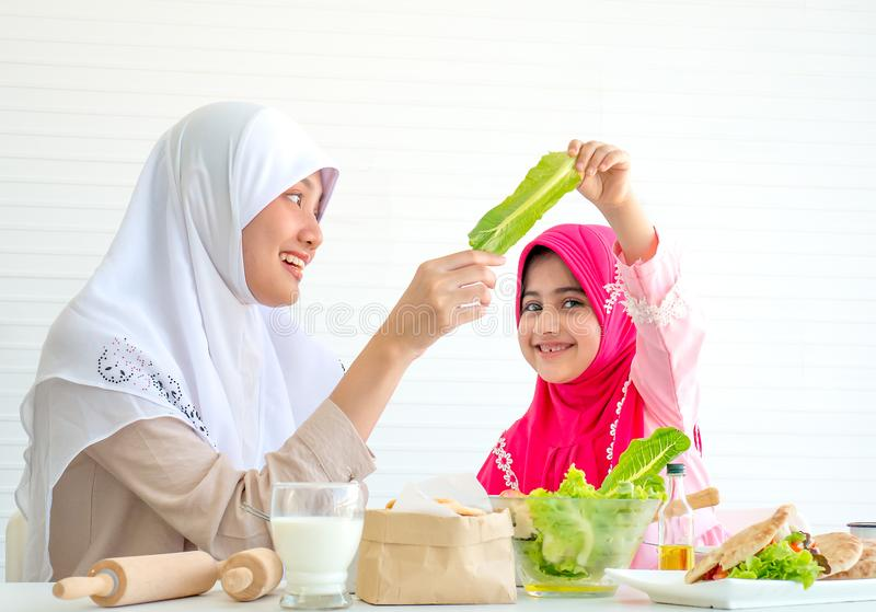 Muslim mother discuss and teach about vegetable for food to her little girl with white background stock photos