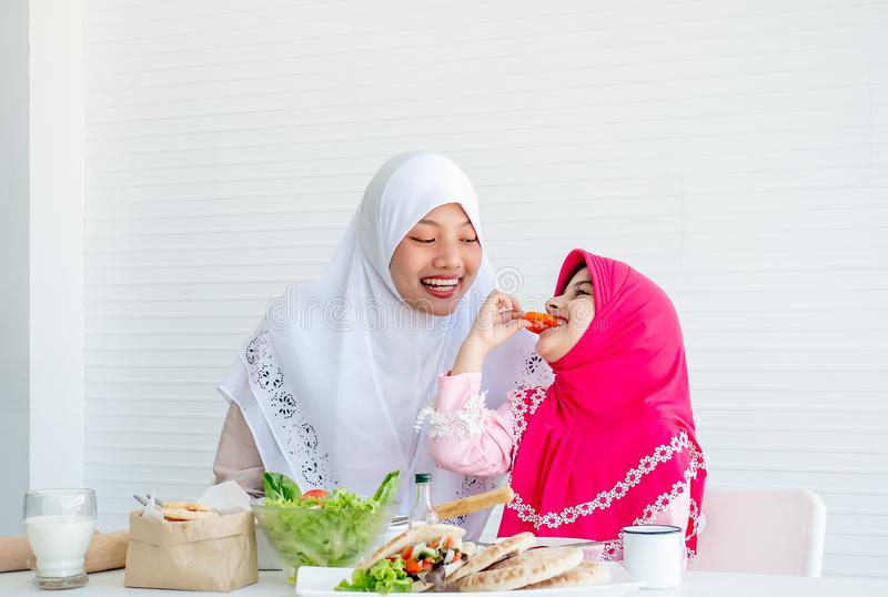 Muslim mother has action for motivating her daughter to eat vegetable, especially fresh tomatoes for good health.  stock photos