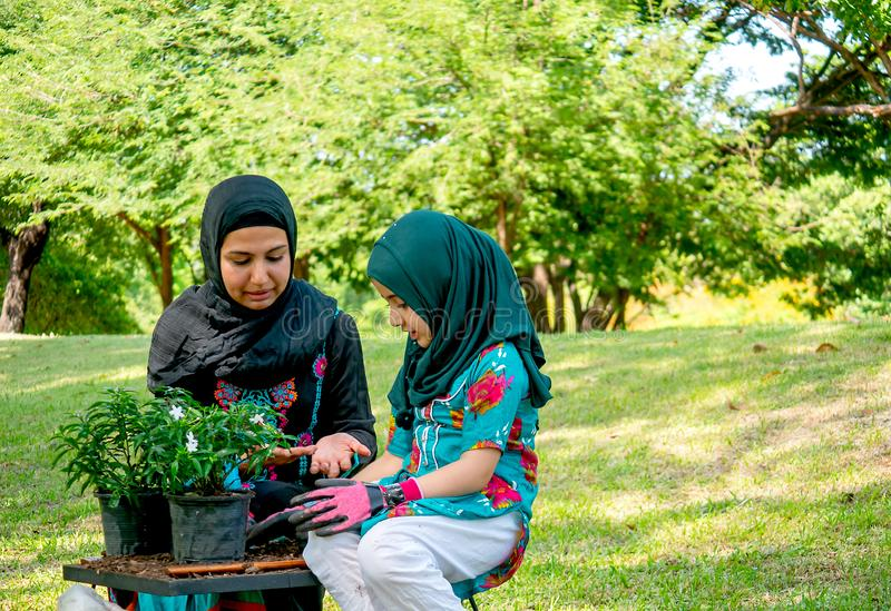 Muslim mother help and teach her daughter to grow and plant a tree in the garden stock image