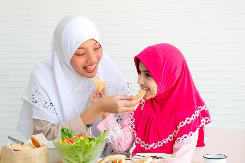 Muslim mother and her daughter are eating cookies together with a bowl of vegetable salad on white background royalty free stock images